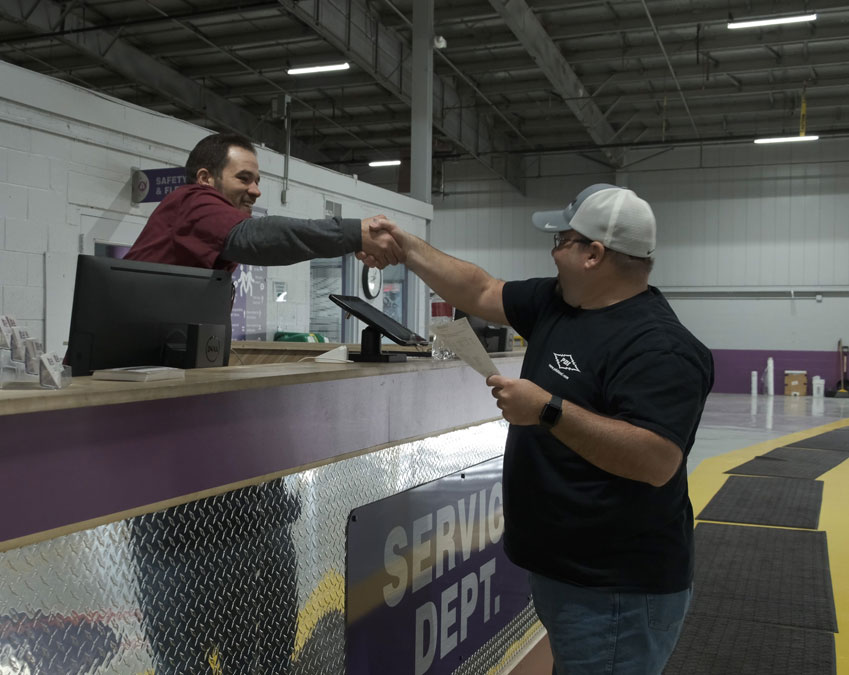Truck driver shaking hands with an ADICA employee.